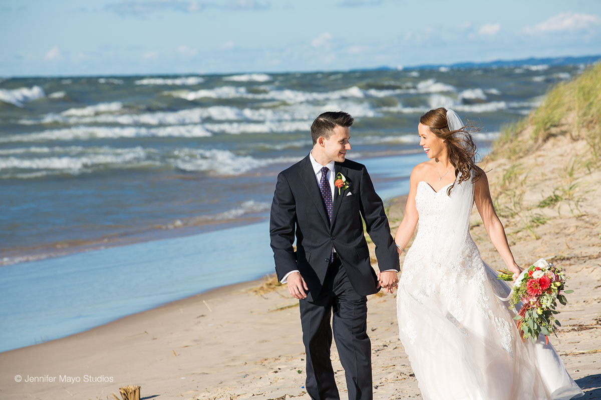 Bride and Groom walking on Silver Beach in St. Joseph, MI